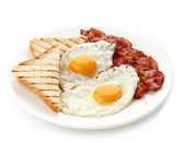 Breakfast with fried eggs, bacon and toasts — Stock Photo