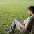 Stock Photo: Young man reading e-book