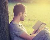 Young man reading e-book — Stock Photo