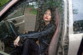 Girl in the car in the rain — Stock Photo