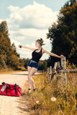 Hitchhiking girl in shorts — Stock Photo