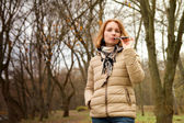 Girl with the electronic cigarette in the park autumn — Stock Photo