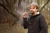 Man with the electronic cigarette in the park autumn — Stock Photo