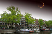 Solar Eclipse over the city Amsterdam. Elements of this image fu — Stock Photo