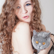 Beautiful naked woman holding a cat in her arms — Stock Photo