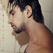 Young handsome man takes a shower closeup — Stock Photo
