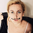 Young woman with painted mustache wearing jacket — Stock Photo