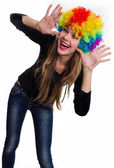 On the head of the cheerful girl multi-colored wig — Stock Photo