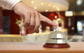 Hand of a man using a hotel bell — Foto de Stock