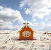 Model of a house with ten dollars on the background — Stock Photo