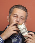 Man lighting his cigar with 100 dollars banknote — Stock Photo