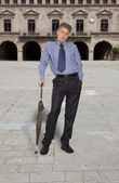 Full lenght of businessman holding an umbrella on background cit — Stock Photo