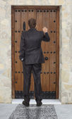 Businessman knocking at a wooden door — Stock Photo