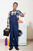 Portrait of an happy plumber against the washing machine — Stock Photo