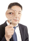 Businessman looking a magnifying glass — Stock Photo