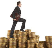 Businessman goes up coins — Stock Photo