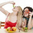 Girlfriends cheerfully play with meal behind table — Stock Photo #13549838
