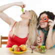 Stock Photo: Girlfriends cheerfully play with meal behind table