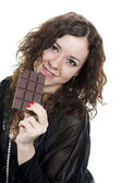 Young curly girl in black eating chocolate — Stock Photo