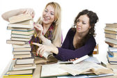 Isolated on white two girls with books on the table — Stock Photo