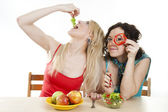 Girlfriends cheerfully play with meal behind a table — Stock Photo