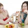 Girlfriends cheerfully feed each other with healthy food — Stock Photo