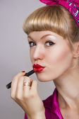 Girl makes up lips with red lipstick — Stock Photo