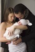 Jonge gezin met de baby thuis — Stockfoto