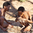 Two bushmen hunters has kindle a fire - Stock Photo