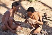 Two bushmen hunters has kindle a fire — Stock Photo