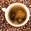 Cup of coffee and coffee-beans background — Stok fotoğraf