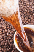 Pouring coffee and coffee-beans — Stock Photo