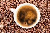Cup of coffee and coffee-beans background — Stockfoto
