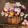 Bouquet of spring flowers in a basket — Stock Photo