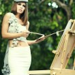 Woman is painting in green garden. — Stock Photo