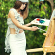 Fashion woman is painting. Open air session. — Stock Photo