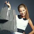 Shopping woman holding bags, isolated on gray studio background. — Stock Photo #12759628
