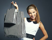 Shopping woman holding bags, isolated on gray studio background. — Stock Photo