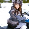 Smiling young woman riding a snowmobile — Stock Photo #13189943