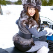 Smiling young womriding snowmobile — Stock Photo #13189943