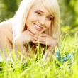 Beautiful young woman relaxing in the grass — Stock Photo #13218857