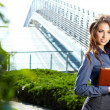 Businesswoman standing outside a modern house — Stock Photo