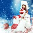 Winter portrait of a santa woman with a christmas gift — Stock Photo #13878802