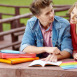 Couple of students holding a notebook outdoors and smiling - Stock Photo