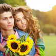 Happy young couple spending time outdoor in the autumn park — Stock Photo