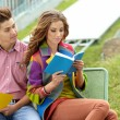 Stock Photo: Couple of students with sitting at campus park and reading book