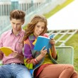 Couple of students with sitting at campus park and reading book — Stock Photo