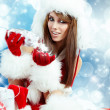 Winter portrait of a santa woman with a christmas gift — Stockfoto #13899497