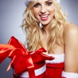 Winter portrait of a santa woman with a christmas gift — Stock Photo #14448407