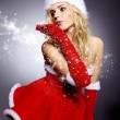 Winter portrait of a santa woman with a christmas gift — Stock Photo #14448679